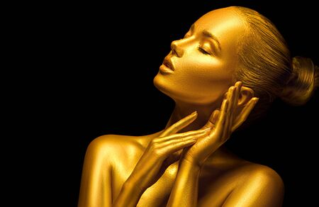 Photo for Model girl with shiny golden professional makeup over black. Beauty sexy woman with golden skin. Fashion art portrait closeup. Gold jewellery - Royalty Free Image