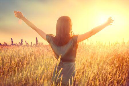 Photo pour Happy autumn woman raising hands over sunset sky, enjoying life and nature. - image libre de droit