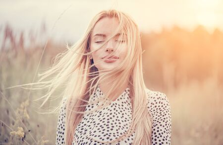 Close Up Portrait of beauty girl with fluttering white hair enjoying nature outdoors, on a field. Flying blonde hair on the wind. Breeze playing with girl's hair. Beautiful young woman face closeup