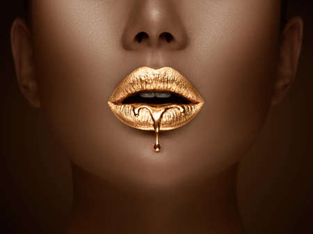 Photo pour Golden lipstick closeup. Liquid metal dripping from gold lips. Beautiful makeup. Sexy lips, bright liquid paint on beauty African American model girl's mouth, close-up. Lipstick. - image libre de droit