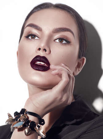 Photo pour Beauty Fashion model girl with dark lips portrait, wearing stylish sexy woman portrait with perfect makeup, trendy accessories and fashion wear. Beauty trends. Perfect skin. White background - image libre de droit