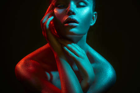 Photo pour Fashion model woman in colorful bright sparkles and neon lights posing in studio, on black, portrait of beautiful sexy girl, trendy glowing sequins make-up. Art design make up. Glitter Vivid makeup - image libre de droit