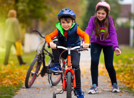 Photo pour Autumn day. Sister teaches her little brother to ride a bike and rejoices at his success. Family and healthy lifestyle. High quality photo - image libre de droit