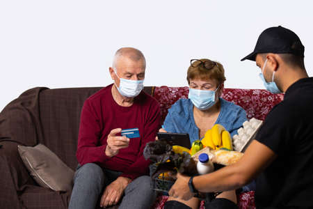An elderly family who ordered groceries online through courier delivery and pay by credit card. Senior online concept and pandemic concept