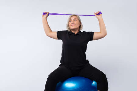 Senior women doing exercises at home using fitness rubber bands on a fitness ball. Photo on a white background.