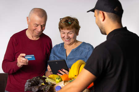The older family pays by credit card for the groceries ordered by the courier service. White background. High quality photo