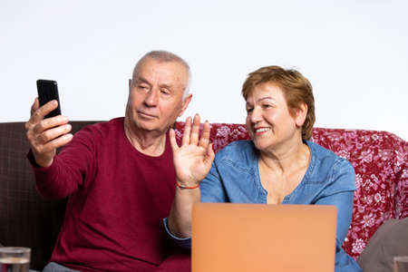 An elderly couple is talking on video while sitting at home. The woman waves her hand in greeting. High quality photo