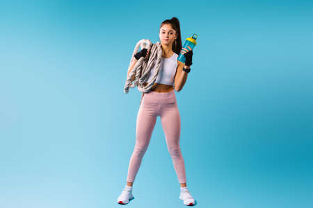 Photo for A muscular fitness girl in sport tight leggings holds a rope knot and a protein shake on her shoulder. Posing against a blue background with empty space. - Royalty Free Image