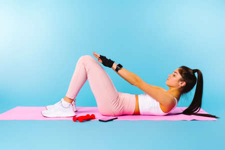 Photo for Exercise on the pink fitness mat. The brunette girl shakes the press. Blue background with return blank space. - Royalty Free Image