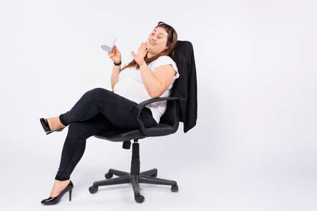 Photo for A happy business woman of large sizes sits in a leather black office chair with a cup of her favorite coffee. White background with side space. - Royalty Free Image