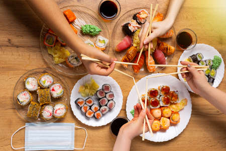 Photo pour High standard sushi delivery. Asian food recommendations, family imitates sushi stick star. Sushi diner gathers friends. Japanese food concept and protective mask. - image libre de droit