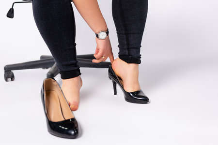 Photo for Cropped photo of female hands putting black, fashion , lacquer heeled shoes on her foot. Businesswoman wearing formal shoes in office, gray background - Royalty Free Image