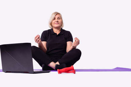 Foto de Middle aged senior 50s woman learning meditate at home watching live online tv yoga class tutorial on website looking at laptop pc doing virtual training fitness workout exercises. High quality photo - Imagen libre de derechos