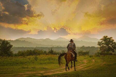 Photo pour Silhouette Cowboy riding a horse under beautiful sunset - image libre de droit