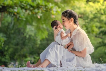 Photo pour Beautiful mother and baby in an Asian park - image libre de droit