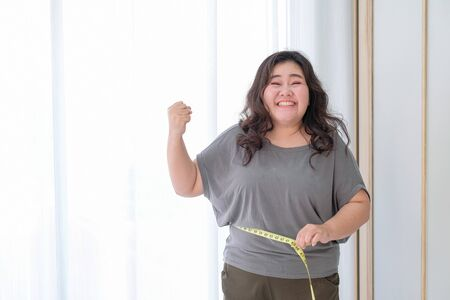 Photo pour Asian obese women are happy because of size reduction after checking with tape measure. - image libre de droit