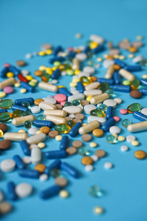 Spilled colored medications and pills on a blue background. Pharmacology and medicine struggle for health. Drug addiction. Treatment of various diseases
