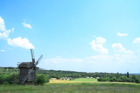 Photo pour Landscape on a summer day against the backdrop of a beautiful ancient village with beautiful houses and mills. Stock photo for design - image libre de droit