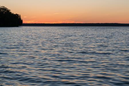 Lake Manitou shoreline sunset landscape with cedar trees and orange sky