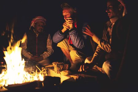 Photo pour Wadi Rum Desert, Jordan. Circa November, 2019. A group of people keeping themselves warm on a very cold night in the desert. - image libre de droit