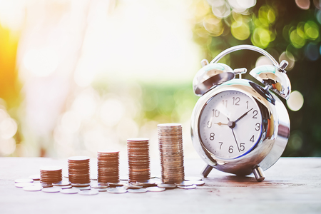 Foto de Close up of time and money with green bokeh background ,Business Finance and Money concept,Save money for prepare in the future.time is money concept - Imagen libre de derechos