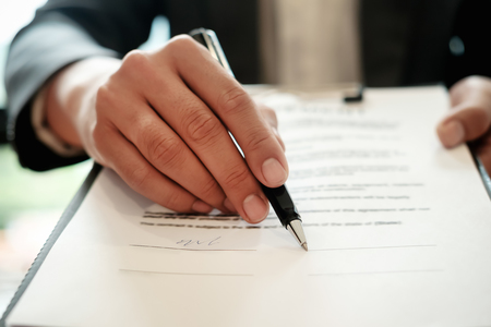 Photo pour Real estate agent with hand putting signing contract,have a contract in place to protect it,signing of modest agreements form in office.Concept real estate,moving home or renting property - image libre de droit