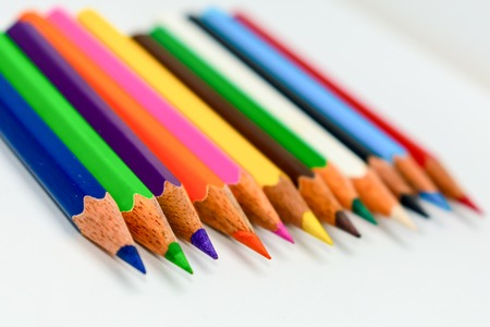 Foto de Close-up of a selection of Multi Colored pencils crayons, stick together arranged in a row line bar graph on white background, flat lay. Selective focus, blur image. Back to school creativity concept. - Imagen libre de derechos