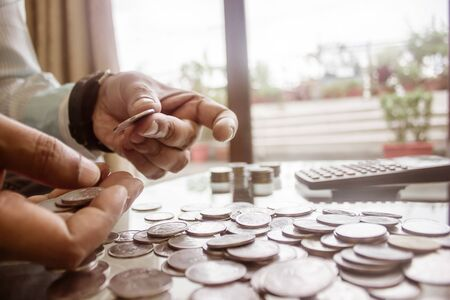 Photo pour Cropped Image Of Businessman counting coins Using Calculator at Desk In Office. Businessperson Hand Counting Coins. Business Finance Savings and Investment concept. Conceptual Save money for future. - image libre de droit