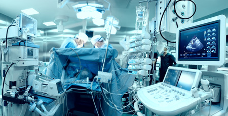 In advanced operating room with lots of equipment, patient and working surgical specialists