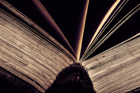 Spine of the open book on black baclground