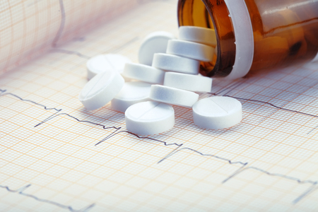 Scattered pills on the ECG test result.