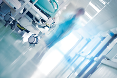 Foto de Medical bed in hospital hallway with professionals hurrying to the emergency case - Imagen libre de derechos