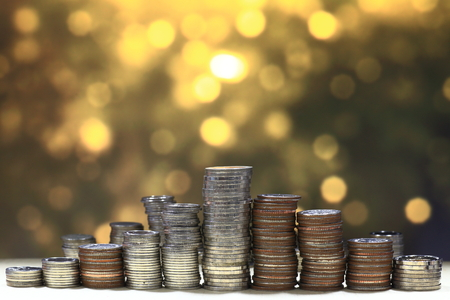 pyramid coin column stacking high, on gold light background. Saving and financial step to success concept.