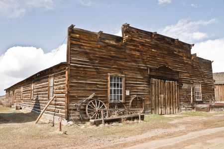 Abandoned mercantile with wagon wheels in front in the ghost town of Nevada City, Montana