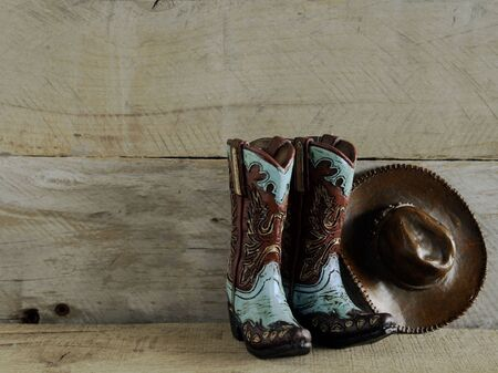 Photo pour cowboy boots and hat on a natural wood background with writing space - image libre de droit