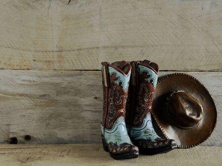 Foto de cowboy boots and hat on a natural wood background with writing space - Imagen libre de derechos