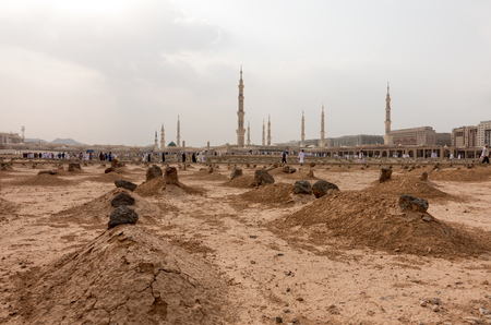Ancient graves in Jannat Al Baqi Cemetery and the Prophet's Mosque al Masjid an Nabawi at the background in Medina, Saudi Arabia
