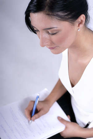 Picture of woman handwriting notes with blue pen.