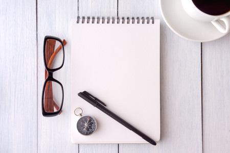 note book,pen,compass,coffee on the desk.top view