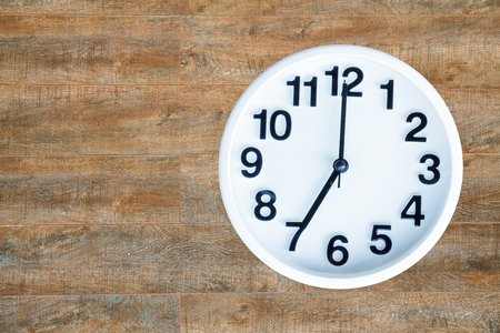 Clock show 7 am or pm on wood background with copy space.