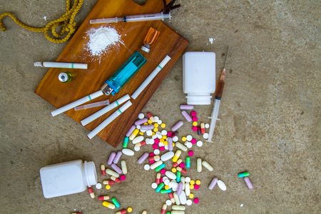 Drugs and Addictions with drug, cigarette, syringe and rope. top view.
