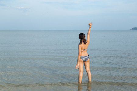 Photo pour Asia teenage girls wearing bikini and hand gesture language translates to love at the beach with copy space. - image libre de droit