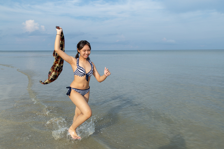Photo pour Asia teenage girls wearing bikini running at the beach by the sea background is blue sky with copy space. - image libre de droit