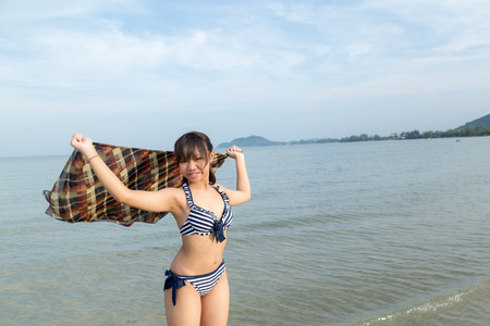 Photo pour Asia teenage girls wearing bikini at the beach with copy space. - image libre de droit