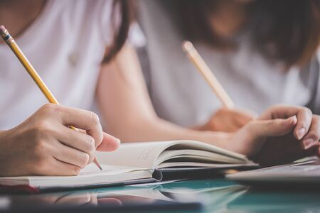 Photo pour Education and back to school concept - Close-up of a student's hand holding a pencil or pen to write on the notebook on the final exam day. - image libre de droit