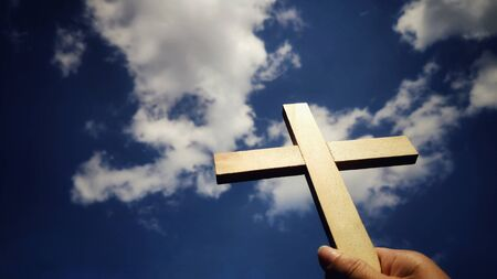 Photo for Lent Season,Holy Week and Good Friday concepts - image of wooden cross raise up to the sky with hand holding it background - Royalty Free Image