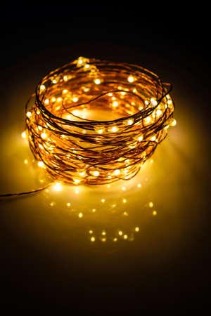 Photo pour Yellow colored light chain for decoration placed on a reflective surface. Portrait view - image libre de droit