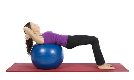 Young woman is doing crunch on a pilates ball