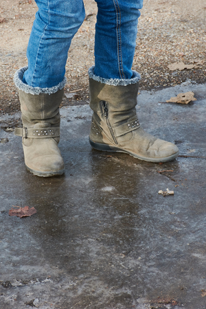 Child legs with jeans and boots on a frozen puddle