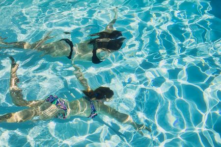 Photo pour two girls swimming underwater in a pool - image libre de droit